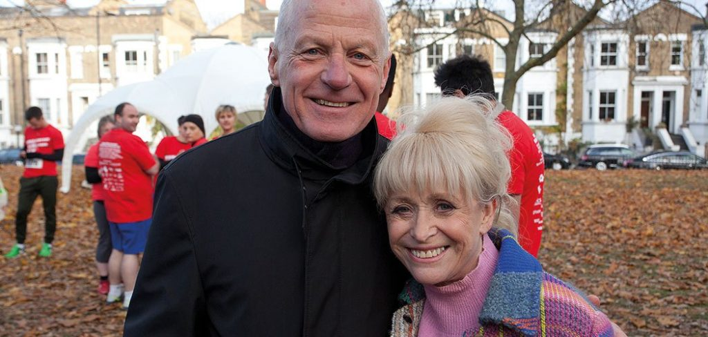 An older man and woman pose and smile together outside at a running event